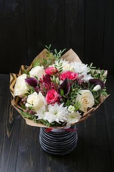 Um buquê de flores sobre um fundo escuro de madeira. bouquet com rosas.