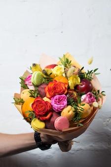 Um buquê de frutas e flores é oferecido por um homem em um fundo branco