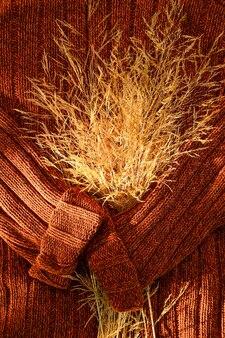 Um buquê de grama seca amarela no fundo de um suéter de malha marrom