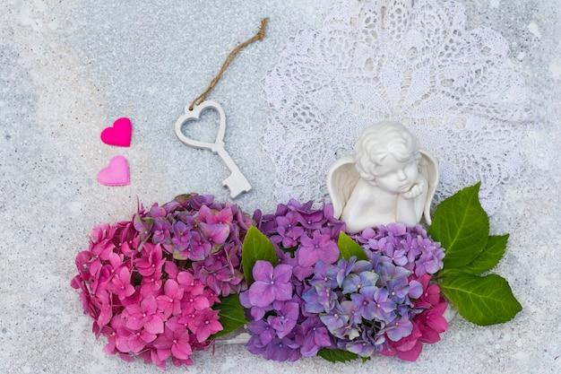 Um buquê de hortênsias, um anjo feito de cerâmica, dois corações e uma chave de madeira