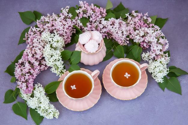 Um buquê de lilás rosa e lilás branco, chá em xícaras e merengues rosa