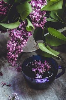 Um buquê de lilás rosa roxo lindo e uma xícara de chá quente