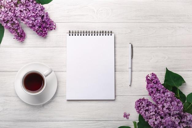 Um buquê de lilases com uma xícara de chá, caderno, envelopes de ofício em quadros brancos. dia das mães