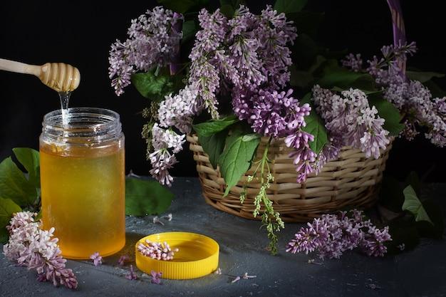 Um buquê de lilases roxos em uma cesta de vime em um escuro ao lado de um pote de mel e uma tampa amarela sobre a mesa.