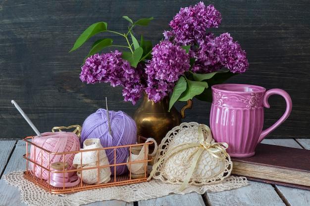 Um buquê de lilases roxos está em um vaso na mesa, um livro, em uma cesta de fio