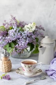 Um buquê de lilases, uma xícara de café