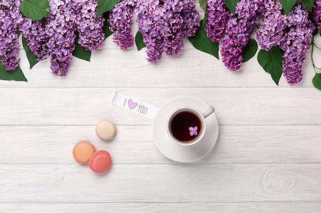 Um buquê de lilases, xícara de chá, nota de amor e macarons em uma mesa de madeira branca