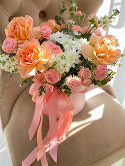 Um buquê de lindas flores de pêssego em uma caixa fica em uma cadeira em uma floricultura. uma composição de rosas, mattiola branca e crisântemo. um presente gentil para um feriado