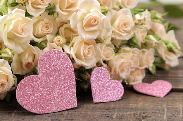 Um buquê de lindas mini rosas tenras em uma mesa de madeira marrom com corações