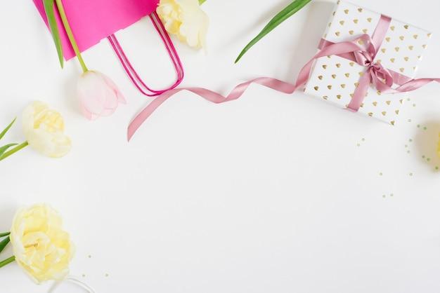 Um buquê de lindas tulipas e um presente em uma vista superior de fundo claro com espaço de cópia. plano de fundo dia das mães, dia internacional da mulher. férias, dê um presente.