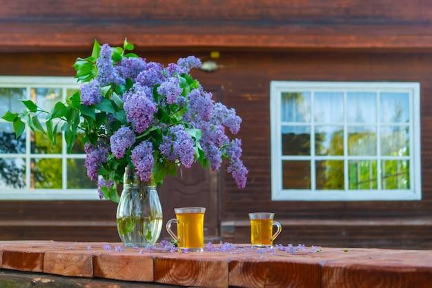Um buquê de lindos lilases em um vaso de vidro fica sobre uma mesa de madeira. chalé de madeira na floresta.