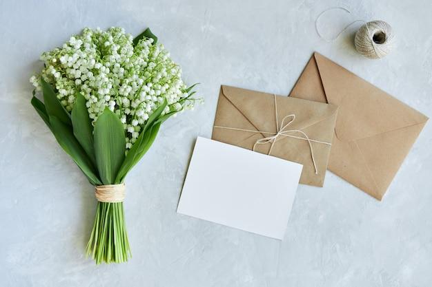 Um buquê de lírios do vale, um envelope com um cartão postal em um fundo azul claro