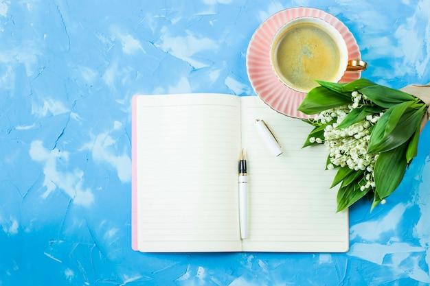 Um buquê de lírios do vale, uma xícara de café e um notebook em uma mesa azul