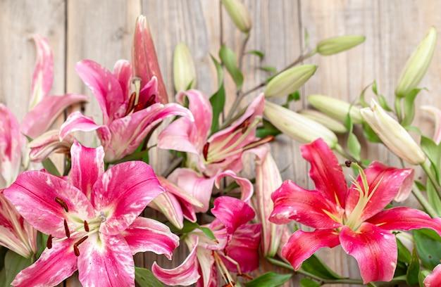 Um buquê de lírios frescos em uma superfície de madeira. conceito de entrega de flores.