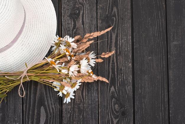 Um buquê de margaridas brancas, flores com orelhas secas em um vaso de papel kraft com um chapéu sobre um fundo preto de madeira em estilo rústico.