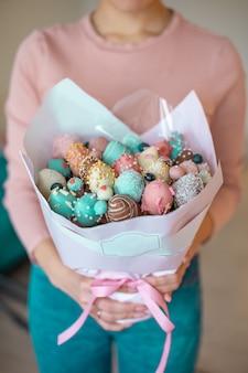 Um buquê de morangos cobertos de chocolate nas mãos de mulher