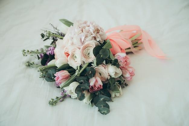 Um buquê de noiva em uma cama