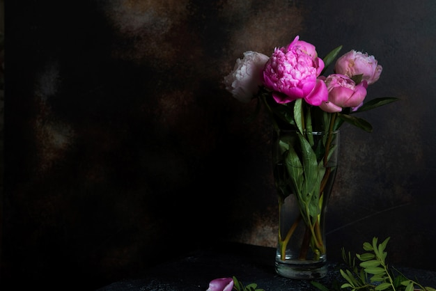 Um buquê de peônias rosa fica em um fundo escuro. imagens criativas para papel de parede e interior.