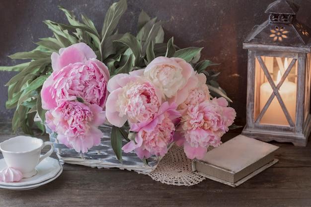 Um buquê de peônias rosa, uma vela em um candelabro na forma de uma lanterna, um livro, um copo