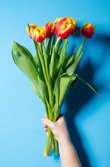 Um buquê de primavera linda de tulipas na mão de uma mulher.