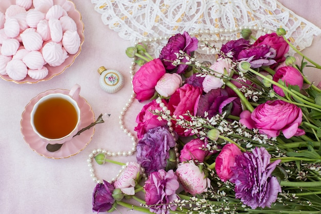 Um buquê de ranúnculo, uma xícara de chá, merengue, um leque e um frasco de perfume