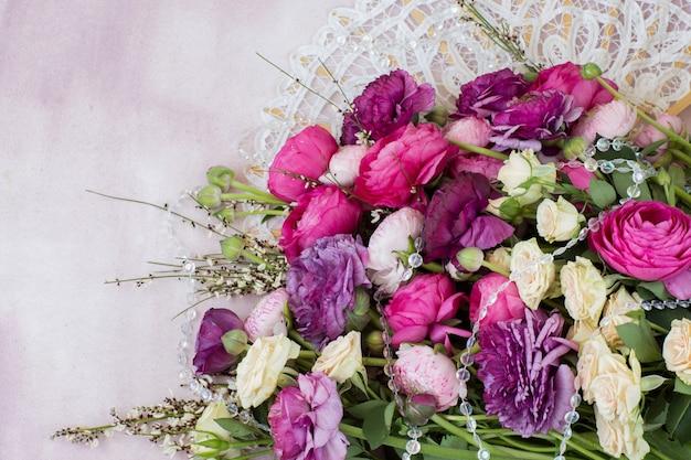 Um buquê de ranúnculos, rosas e um leque branco