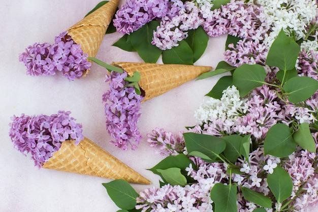 Um buquê de rosa lilás e branco lilás, três cones de bolacha com lilás
