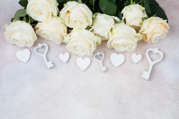 Um buquê de rosas brancas, chaves, corações