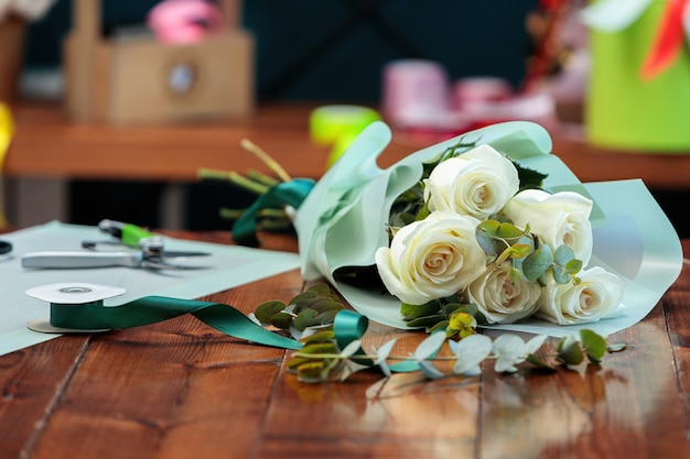 Um buquê de rosas brancas em uma embalagem de papel encontra-se sobre uma mesa de madeira.