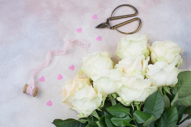 Um buquê de rosas brancas, tesoura velha, corações rosa e fita de renda