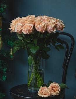 Um buquê de rosas com folhas verdes dentro de um vaso