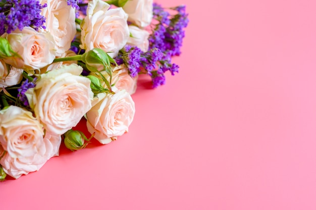 Um buquê de rosas creme e flores roxas brilhantes em plena floração em um fundo rosa com espaço para texto. cartão de felicitações