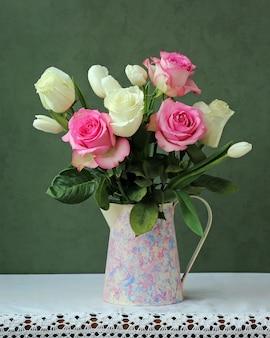 Um buquê de rosas e tulipas em um jarro na mesa