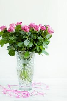 Um buquê de rosas em um vaso de cristal