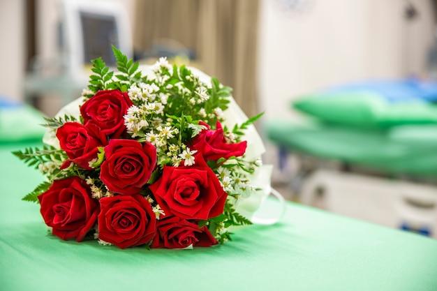 Um buquê de rosas em uma cama de hospital