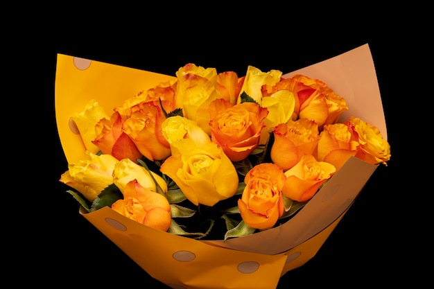 Um buquê de rosas laranja em um pacote de presente é isolado em um fundo preto. foto de alta qualidade