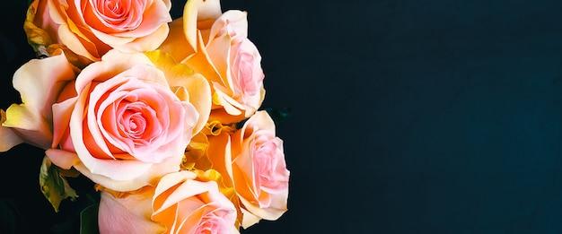 Um buquê de rosas lindas, frescas, brilhantes sobre um fundo azul escuro.
