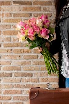 Um buquê de rosas nas mãos de uma mulher com uma mala perto de uma parede de tijolos