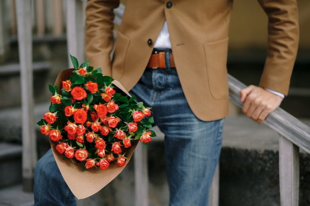 Um buquê de rosas nas mãos masculinas.