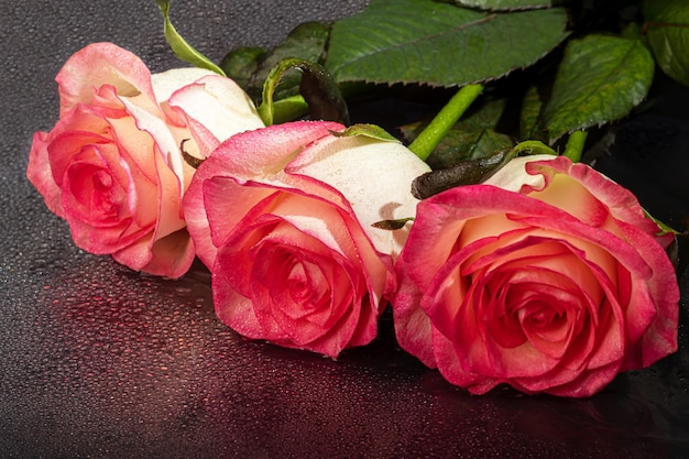Um buquê de rosas para o feriado. dia da mulher, dia dos namorados, dia do nome. sobre um fundo escuro com reflexo. copie o espaço