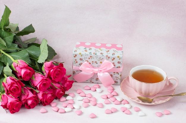Um buquê de rosas, um presente em uma caixa, doces em forma de coração e chá em uma xícara