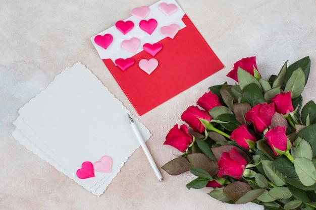 Um buquê de rosas vermelhas, corações de cetim, folhas de papel, uma caneta e um envelope vermelho