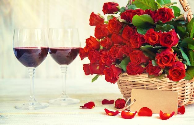 Um buquê de rosas vermelhas e vinho tinto em taças. dia dos namorados. foco seletivo. feriado.