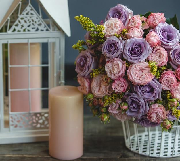 Um buquê de rosas vermelhas e violetas com folhas com velas cor de rosa ao redor
