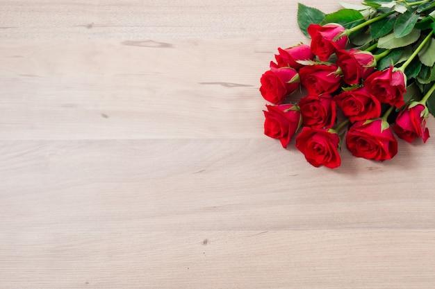 Um buquê de rosas vermelhas em um fundo de madeira com espaço para texto