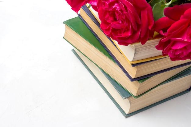 Um buquê de rosas vermelhas em uma pilha de livros sobre uma superfície de pedra clara. conceito de amor pela literatura e romances