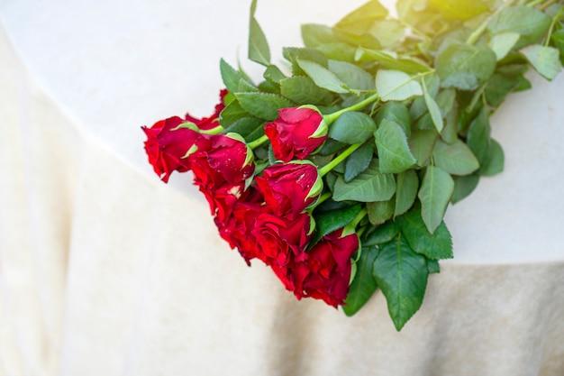 Um buquê de rosas vermelhas está na beira da mesa