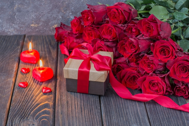 Um buquê de rosas vermelhas, um presente em uma caixa, uma fita vermelha e velas