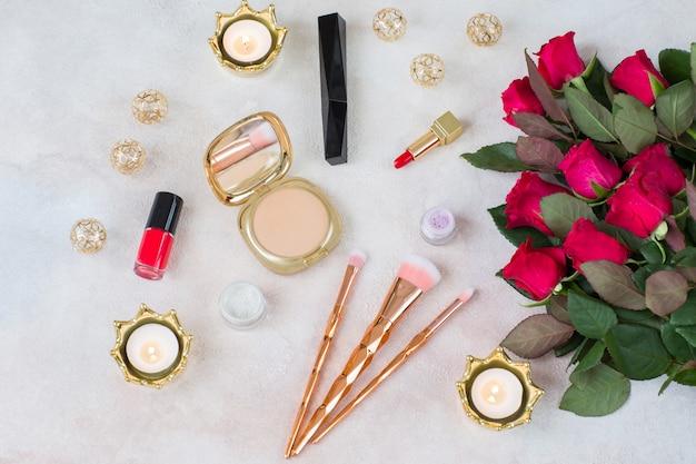 Um buquê de rosas vermelhas, velas, itens de decoração e maquiagem: pincéis, batom, pó, rímel, sombra para os olhos