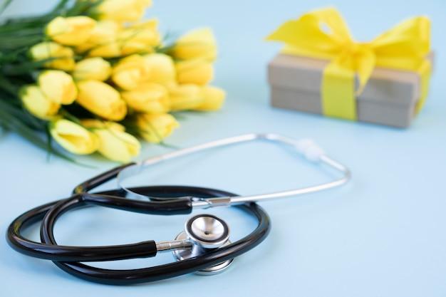 Um buquê de tulipas amarelas com um estetoscópio e um presente em azul